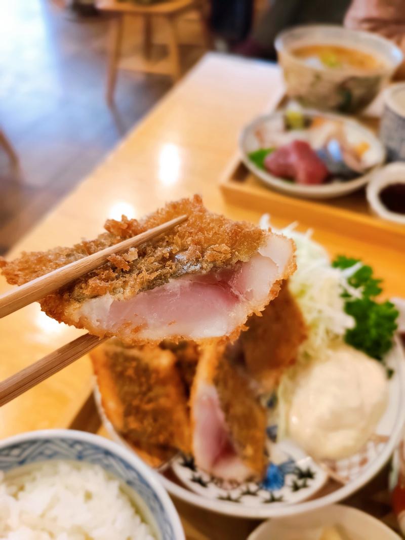 氏ノ木の究極のアジフライ定食を箸で持ち上げた写真